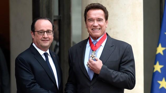Schwarzenegger posiert stolz mit seiner Auszeichnung neben Frankreichs Präsident Hollande. (Bild: AFP)