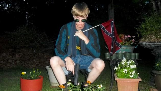Dylann Roof auf einem seiner zahlreichen schaurigen Bilder mit Waffe und Konföderierten-Flagge (Bild: AP)