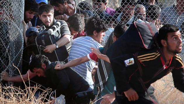 Flüchtlinge durchbrechen einen Grenzzaun zwischen Syrien und der Türkei.