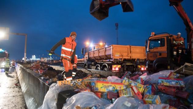 Mitarbeiter der ASFINAG säuberten gemeinsam mit Feuerwehrleuten die Autobahn von den Saftpackerln. (Bild: Werner Kerschbaummayr)