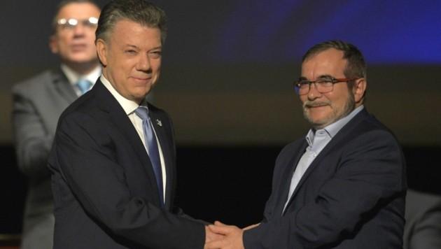 Präsident Santos (links) und FARC-Führer Londono bei der Unterzeichnung des Vertrags (Bild: APA/AFP/LUIS ROBAYO)