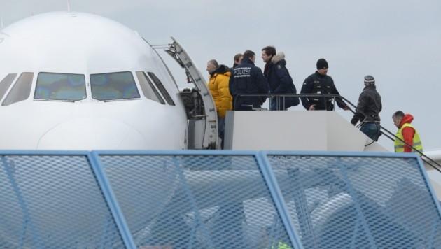 Abschiebung aus Deutschland: Flüchtlinge werden von Polizisten in ein Flugzeug eskortiert. (Bild: APA/EPA/PATRICK SEEGER)