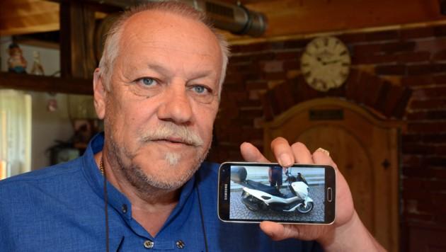 Spörr zeigt ein Bild von seiner Vespa, die er erst in zwei Monaten mit viel Aufwand abholen darf. (Bild: Andreas Fischer)