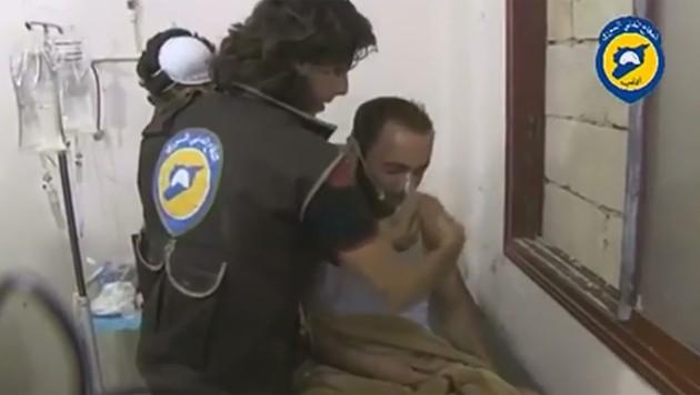 Ein Mann in Atemnot bekommt von einem Helfer eine Atemschutzmaske gereicht.