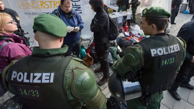 Deutsche Polizisten kontrollieren die Papiere von Flüchtlingen.