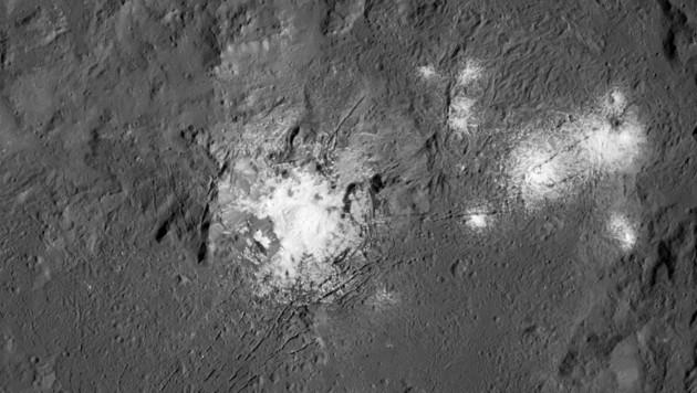 Nahaufnahme zeigt Risse und helle Flecken im Occator-Krater.