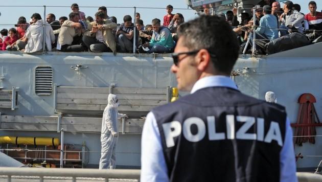 Ein italienischer Polizist wartet auf die Ankunft von Flüchtlingen in Sizilien. (Bild: APA/AFP/GIOVANNI ISOLINO)