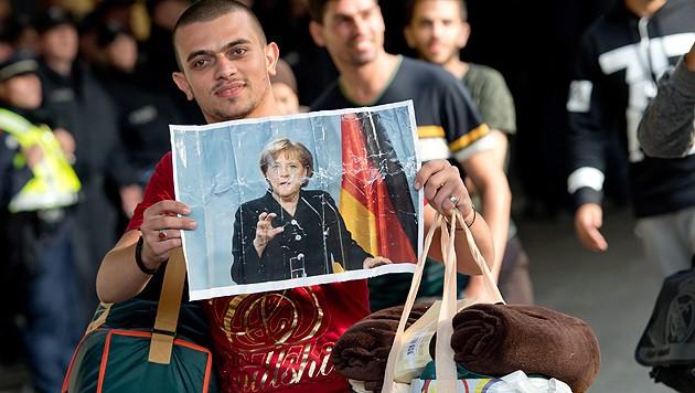 Bahnhof München: ein ankommender Flüchtling mit einem Bild von Kanzlerin Merkel (Bild: APA/EPA/Sven Hoppe)