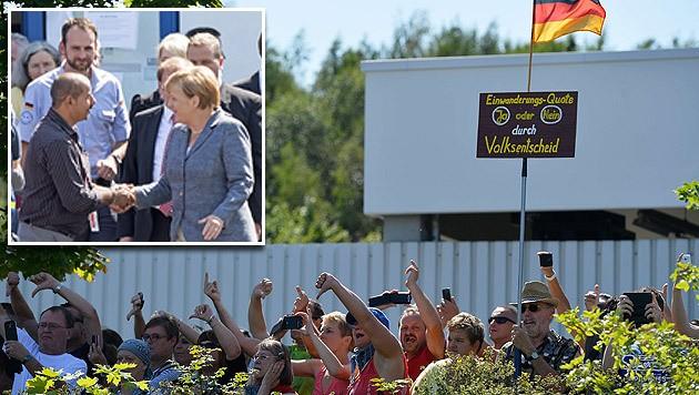 Merkel beim Handshake mit einem Flüchtling; Protest gegen die Asylpolitik der Regierung (Bild: AFP, AP)