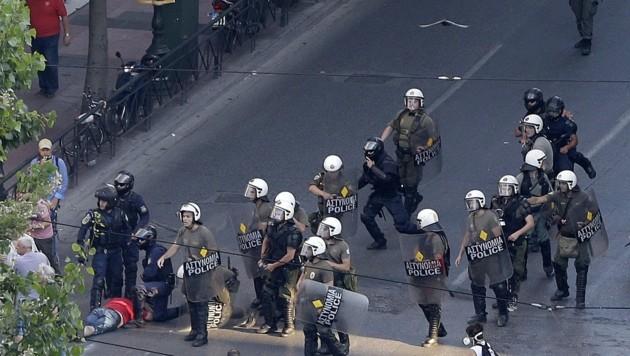 Einige vermummte Störenfriede mussten von der Polizei zur Räson gebracht werden. (Bild: AP)