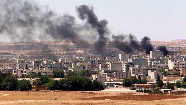 Rauchwolken über der Kurdenstadt Kobane nach einem Angriff... (Bild: APA/EPA/STR)