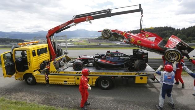 Nach dem Crash zwischen Alonso und Räikkönen werden beide Autos abtransportiert. (Bild: APA/ERWIN SCHERIAU)
