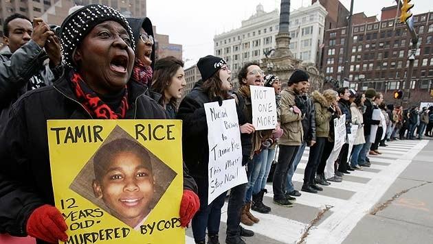 Eine Frau hält bei einer Demonstration gegen Rassismus ein Bild von Tamir Rice in den Händen. (Bild: AP)
