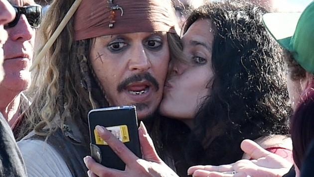 Johnny Depp ließ sich von einem Fan niederknutschen. (Bild: APA/EPA/DAVE HUNT)