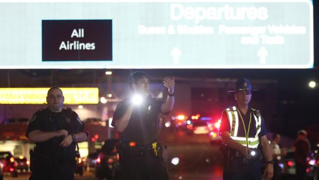 Polizisten riegelten nach dem Angriff das Flughafenareal großflächig ab.