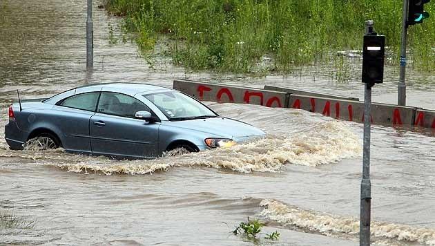 Ein Autofahrer lenkt in der serbischen Hauptstadt Belgrad seinen Wagen durch die Fluten. (Bild: APA/EPA/Koca Sulejmanovic)