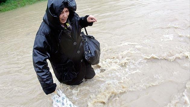 Eine Frau müht sich in Belgrad über eine vollkommen überschwemmte Straße. (Bild: APA/EPA/Andrej Cukic)